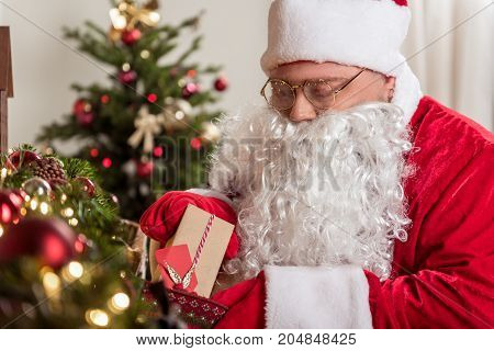 Portrait of kind old bearded man in red and while costume hiding present into decoration at Christmas night