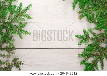 Christmas background with copy space, top view on pine tree twigs frame on white rustic wood table surface. Xmas decorations, winter holidays concept