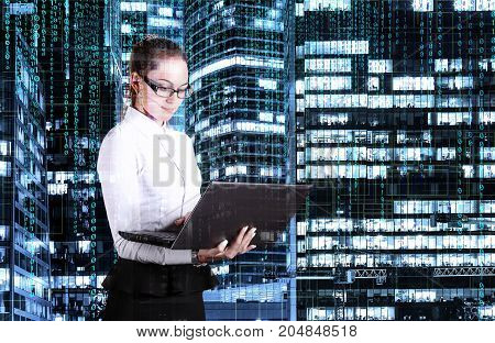 business lady with laptop in hand on the background of night skyscrapers covered with binary code