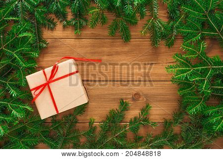 Gift wrapping background. Christmas present in paper decorated with satin ribbon. Winter holidays concept copy space. Top view of rustic wood table with fir tree branches frame