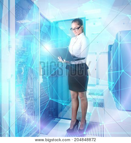 young lady engineer in office clothes standing with laptop in hands on background the server room of data center and futuristic design of the concept big data