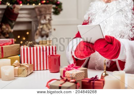 Close up of Father Frost hands in red gloves holding digital tablet. Present boxes on desk