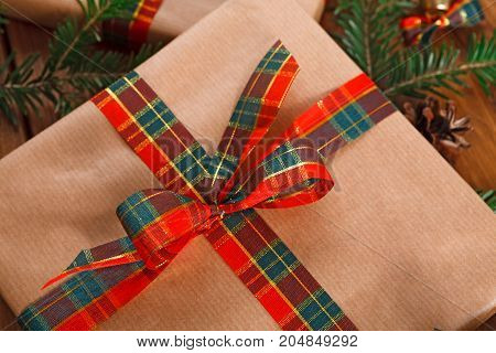 Gift box wrapped with craft paper. Christmas, new year and winter holidays concept. Crop, closeup