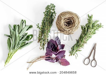 flat lay with fresh herbs and greenery for drying and making spices set on white kitchen table background pattern