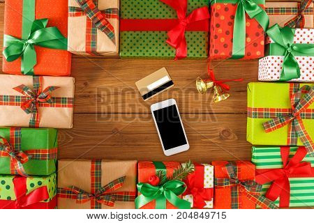 Preparing for holidays background. Gift boxes frame, mobile and credit card on wood. Seasonal sales, online sopping, presents for any holiday concept. Top view, flat lay, copy space