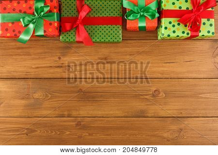 Gift boxes frame, top view with copy space on wood table background. Border of colored packages with red, green ribbons for christmas, valentine day or birthday