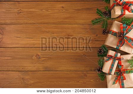 Gift boxes and fir tree twigs border, top view with copy space on wood table background. Frame of colored packages with red, green ribbons for christmas, valentine day or birthday