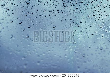Drops of rain on a blue window glass. Close up detail of a wet surface water with copy space