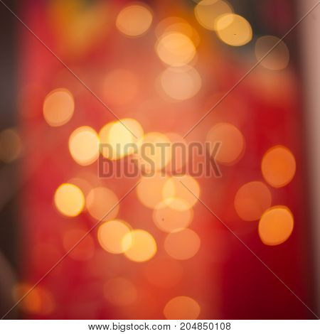 Red Christmas background with yellow bokeh and twinkled defocused lights. Festive blur background