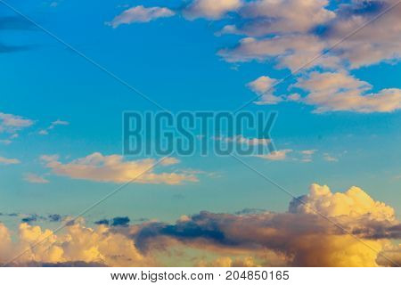 Background, texture of blue sky with white, yellow, pink clouds