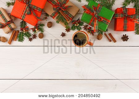 Cosy christmas eve background. Colorful handmade gift boxes border, nuts and spices, black hot coffee cup on white wood. Preparing for winter holidays concept, copy space, top view