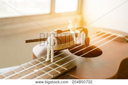 Miniature figurines Businessman sitting on ukulele with Graduation cap. Ukuleles is member lute family instruments with nylon stringed played with bare thumb fingertips. Concept of Music Education.