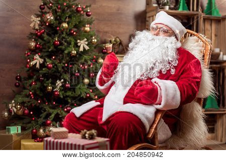 Christmas time. Portrait of happy Santa Claus ringing the jingle bell and smiling. He is sitting on armchair near fir-tree