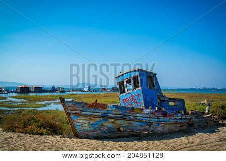 abandoned old fishing boat lying on sand in comporta alentejo Portugal.