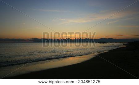 kızıl bir gün batımında deniz, gökyüzü ve sahil
