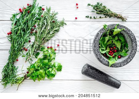 Food set with various herbs and berries for making spices and mortar on white wooden background top view