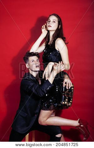 young fashion style couple man and woman on red sexy background, luxury stuff, lifestyle modern people sale concept close up
