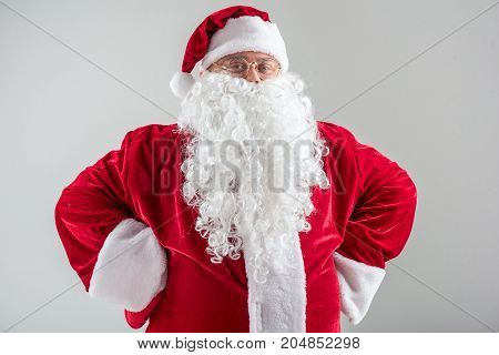 Waist up portrait of proud bearded Santa Claus standing with arms akimbo. He is looking at camera and smiling. Isolated on grey background