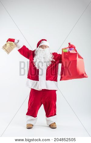 I have got lots of presents. Full length portrait of joyful Santa Claus showing sack and gift box with excitement. He is standing in red and white costume. Isolated