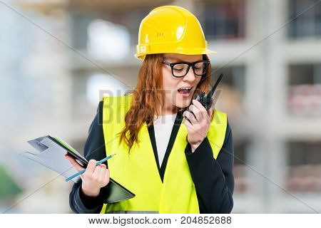 Female Brigadier Wearing Helmet And Waistcoat With Walkie-talkie At Construction Site