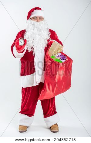 It is almost midnight. Full length portrait of excited old Santa Claus showing clock time. He is standing and holding red sack full of gifts. Isolated
