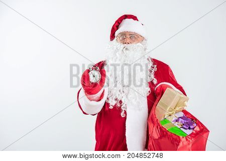 Portrait of serious Santa is ready to give presents. He is showing time on clock and holding bag with present boxes. Isolated and copy space