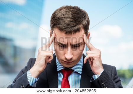 Portrait Of A Businessman With A Strong Headache And Troubles In Business In Office