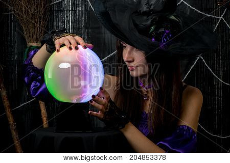A Girl In A Black Hat Works As A Fortune-teller, Looks Carefully Into The Ball Of Fate