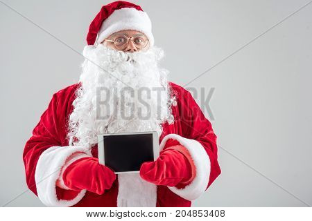 Merry Christmas. Portrait of kind Santa Claus holding digital tablet. He is standing in red and white costume. Isolated and copy space