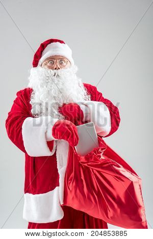 Portrait of shocked Santa Claus putting tablet in red bag. He is standing and looking forward with surprise. Isolated