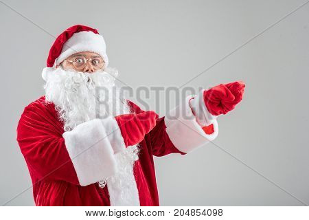 Let me show you something interesting. Waist up portrait of excited Father Frost pointing fingers aside. Isolated and copy space