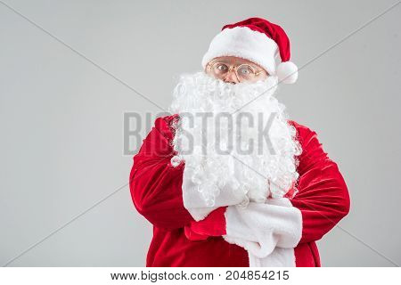 Portrait of serious mature Santa Claus standing with crossed arms. Isolated and copy space in left side
