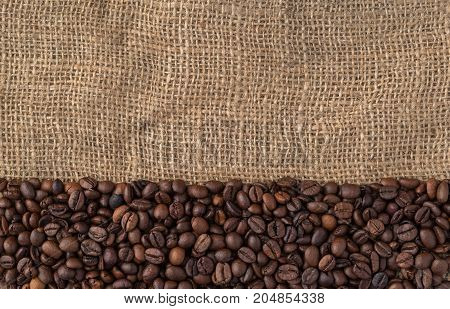 Mixture of different kinds of coffee beans on jute background.