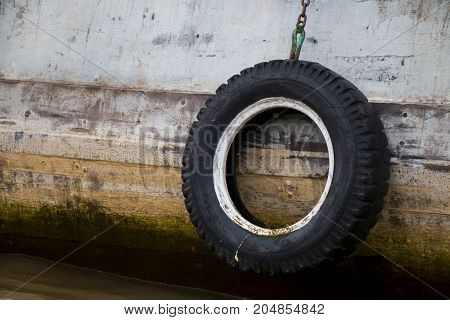 Old tire hanging from wooden boat side.