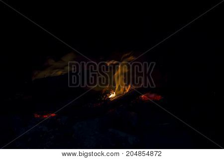 A small flame of a night camp fire
