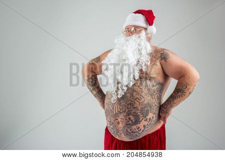 Portrait of cheerful Santa Claus standing with arms akimbo. He has big tattooed bare abdomen. Isolated and copy space