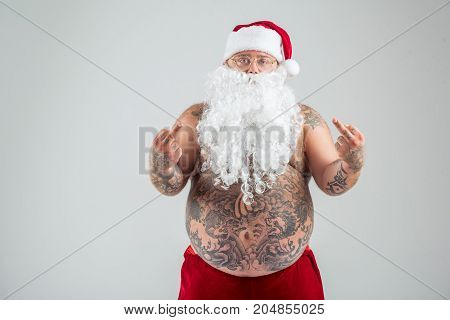 Portrait of aggressive man showing middle fingers to camera. He is standing with naked fat abdomen all in tattoo. Man is wearing Santa Claus hat and beard. Isolated and copy space