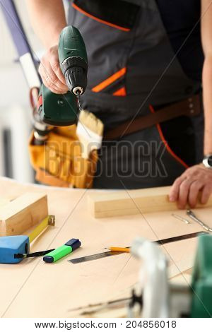 Arms Of Worker Using Electric Drill Closeup