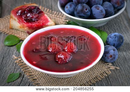 Plum jam in white bowl fresh plums on wooden table