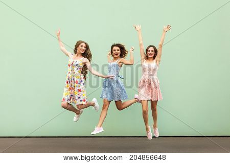 Fasionable Young Adult Woman's Jumping And Hands Up. Looking At Camera And Toothy Smile