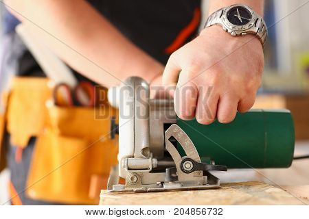 Arms Of Worker Using Electric Saw Closeup