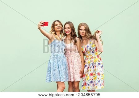 Three Beautiful Sisters In Dress, Macking Selfie On Green Background,