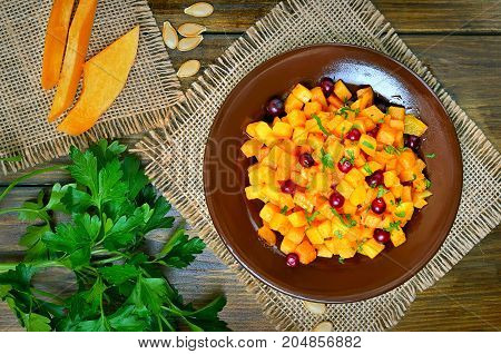 Salad with pumpkin and cranberri on plate top view