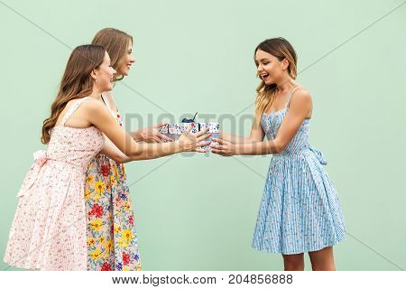 Young Adult Cute Girl Giving Surprise Gift To Hes Pretty Friend.