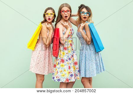 Portrait Of Three Wonder Girls With Packages And New Clothes.
