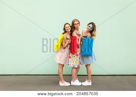 Happiness Beautiful Three Friends In Glasses With Colorful Packets After Shopping