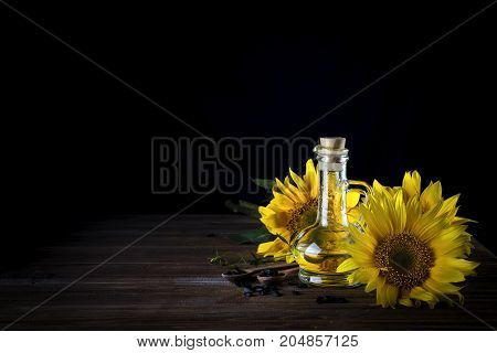 Sunflower oil in bottle glass with seed and flowers on a black wooden background, copy space