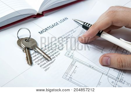apartment keys apartment plan mortgage loan document and human hand