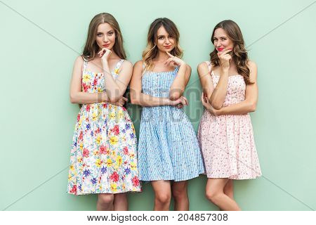 Three Cheerful Girl Planning Something And Playfully Looking At Camera.
