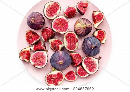 Plate of fresh blue figs on white background top view.